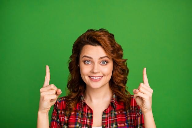 Close-up portret van haar mooie, mooie, vrolijke, vrolijke, golvende meisje met twee wijsvingers omhoog kopieerruimte geïsoleerd over heldere levendige glans levendige groene kleur achtergrond