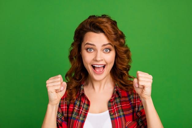 Close-up portret van haar mooie, verbaasde, gelukkige, vrolijke, golvende meisjesfan met een geruit overhemd met vuisten die plezier hebben geïsoleerd over heldere levendige glans levendige groene kleur achtergrond