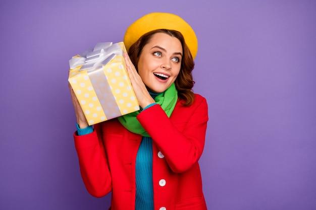 Close-up portret van haar mooie, vrolijke, vrolijke, dromerige verbaasde meisje met golvend haar in handen geschenkdoos gissen wat erin zit geïsoleerd over violet lila paarse pastel kleur achtergrond