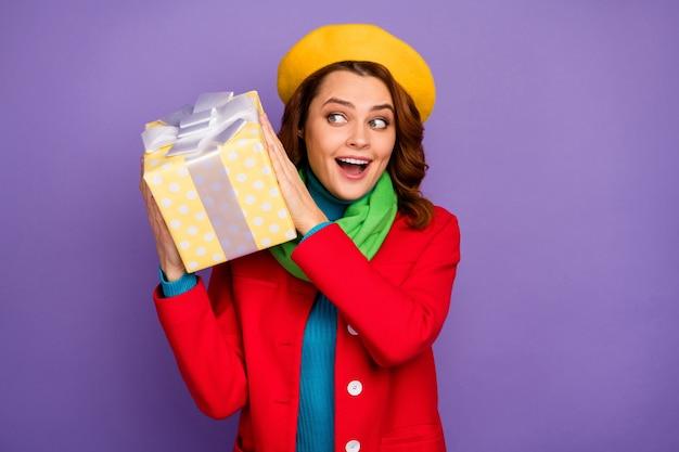 Close-up portret van haar, ze is aardig, vrolijk, vrolijk, blij, opgetogen meisje met golvend haar dat in de doos van de handen houdt en raadt wat er in zit geïsoleerd over violet lila paarse pastel kleur achtergrond