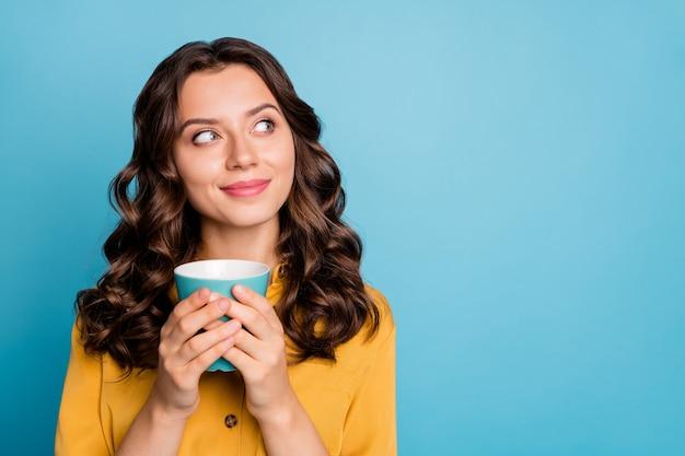Close-up portret van haar, ze is mooi aantrekkelijk vrolijk dromerig nieuwsgierig vrouwelijk golvend haar meisje houdt in handen drinken latte.