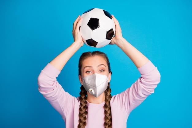 Close-up portret van haar ze leuk aantrekkelijk actief meisje met veiligheid n95 beschermend masker spelen competitie voetbal preventieve maatregelen gezondheidszorg geïsoleerde heldere levendige glans blauwe kleur achtergrond