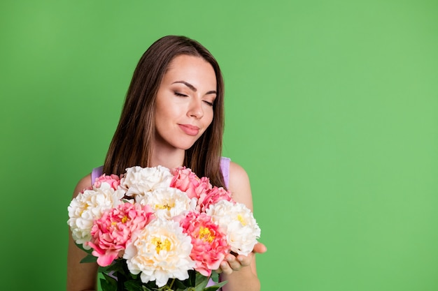 Close-up portret van haar ze leuk aantrekkelijk mooi charmant dromerig vrolijk meisje genieten van feestelijke moeder moederdag in handen ruikende verse bloemen kopiëren ruimte geïsoleerde groene kleur achtergrond
