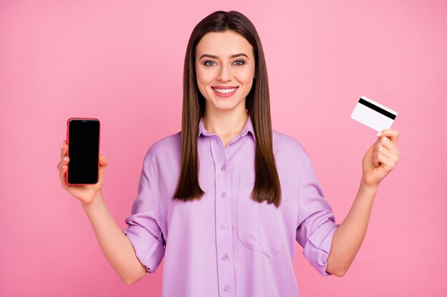 Close-up portret van haar ze leuk aantrekkelijk mooi mooi schattig innemend blij vrolijk vrolijk langharig meisje demonstreren met behulp van mobiele bankkaart kopen online geïsoleerd op roze pastel kleur achtergrond