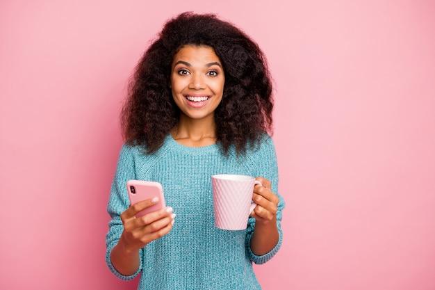 Close-up portret van haar ze mooi aantrekkelijk mooi vrij vrolijk vrolijk golvend meisje met behulp van digitaal apparaat cacao drinken geïsoleerd over roze pastelkleur muur