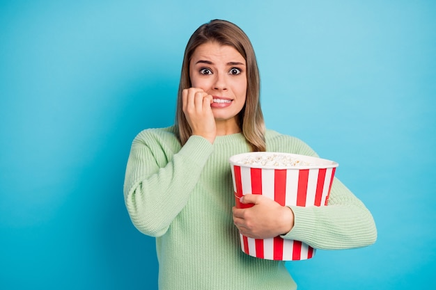 Close-up portret van haar ze mooi uitziende aantrekkelijke mooie bezorgd bang meisje maïs eten kijken naar enge tv-show bijten nagels geïsoleerd over heldere levendige glans levendige blauwe kleur achtergrond