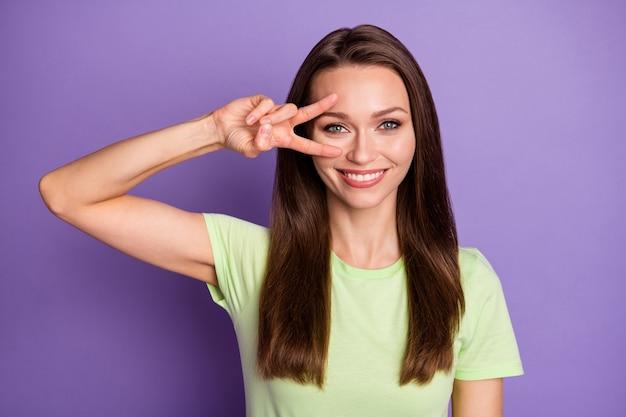 Close-up portret van haar ze mooi uitziende aantrekkelijke mooie mooie vrouwelijke vrolijke vrolijke meisje met v-teken in de buurt van oog geïsoleerd over heldere levendige glans levendige lila violette kleur achtergrond
