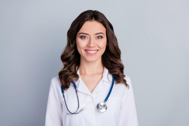 Close-up portret van haar ze ziet er aantrekkelijk mooi vrij schattig vrolijk vrolijk golvend meisje doc kliniek ziekenhuis specialist deskundige geïsoleerd over grijze pastelkleur achtergrond