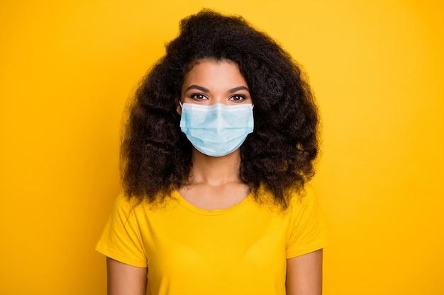 Close-up portret van haar zij gezond golvend meisje met veiligheidsgaas masker stop cov mers ncov-2 china wuhan griep griep griep grippe koorts geïsoleerd helder levendig glans levendige gele kleur achtergrond