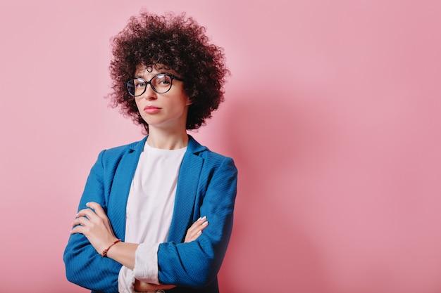 Close-up portret van helder gekrulde vrouw gekleed blauwe jas en bril staat met ernstige emoties op roze