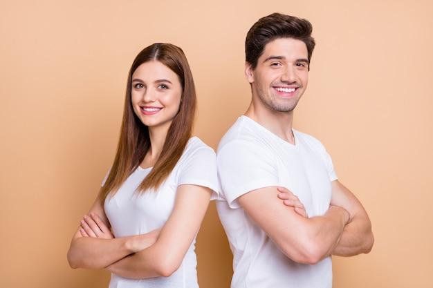 Close-up portret van hem hij haar zij mooie aantrekkelijke vrolijke vrolijke tevreden succesvolle paar dragen witte t-shirt gevouwen armen staande rug aan rug geïsoleerd over beige pastel kleur achtergrond