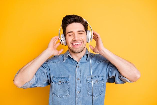 Close-up portret van hem leuk aantrekkelijk vrolijk opgewekt dromerig man luisteren favoriete muziek melodie ritme geïsoleerd over helder levendig glans levendige gele kleur muur