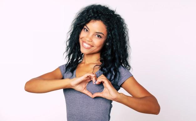 Close-up portret van inhoud afro etnisch meisje met rommelig ravenzwart haar dat breed lacht, met haar handpalmen in de buurt van haar borst met een handhart
