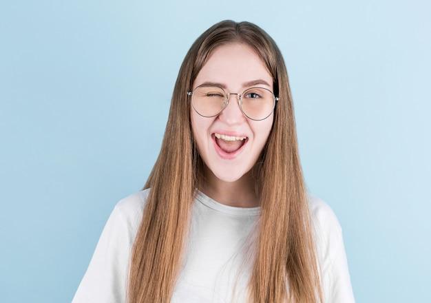 Close-up portret van jong europees meisje. gelukkig vrouw met lachend gezicht knippert op blauw