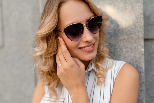Close-up portret van jonge aantrekkelijke stijlvolle blonde vrouw in stad straat in zomer mode stijl jurk dragen van een zonnebril