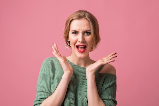 Close-up portret van jonge aantrekkelijke vrouw met geschokt gezichtsuitdrukking, verrast, emotioneel, grappig, geïsoleerd op roze achtergrond, hand in hand, open mond, blij, in de camera kijken