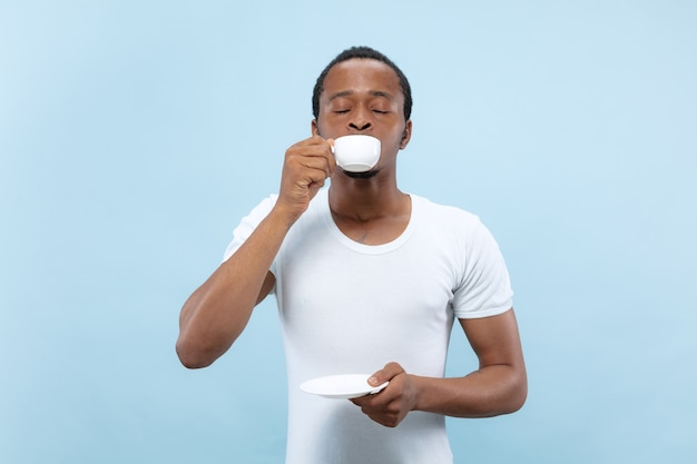 Close-up portret van jonge afro-amerikaanse man in wit overhemd. genieten, koffie drinken, glimlachen.