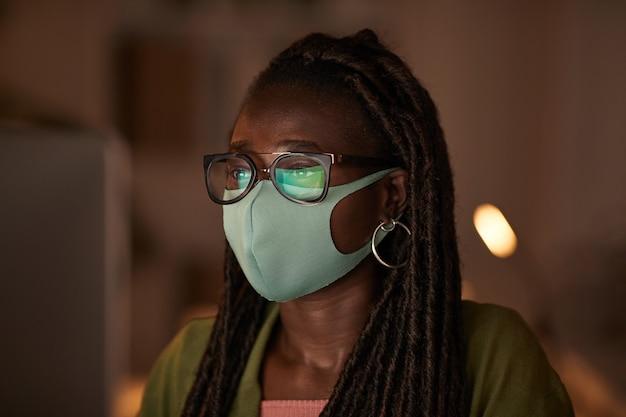 Close-up portret van jonge afro-amerikaanse vrouw masker en bril dragen tijdens het werken met pc in kantoor, kopieer ruimte