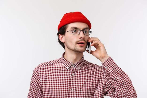 Close-up portret van jonge blanke man in glazen en rode muts, gesprek, vriend rondkijken als zoekende persoon in menigte, smartphone in de buurt van oor houden,