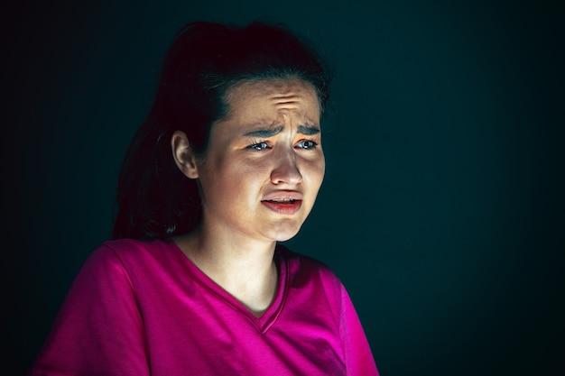 Close-up portret van jonge gekke bang en geschokt vrouw geïsoleerd op donkere achtergrond