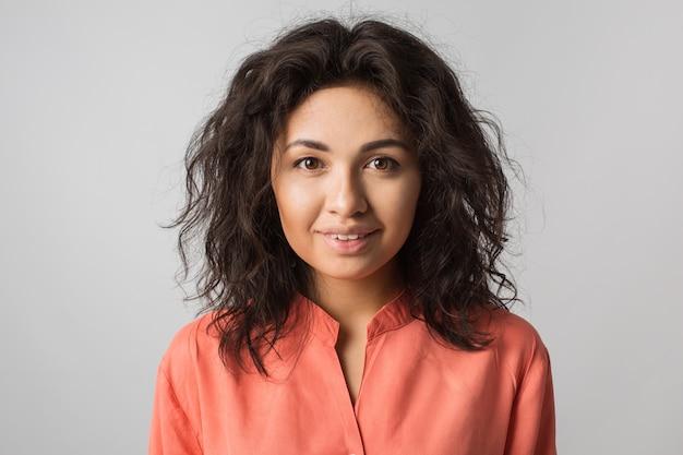 Close-up portret van jonge gelukkig mooie brunette vrouw in oranje shirt, krullend haar, bruine ogen, zomerstijl, natuurlijke look, modetrend`` gemengd ras, geïsoleerd, gebruinde huid