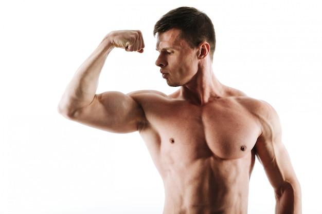 Close-up portret van jonge gespierde man met kort kapsel kijken naar zijn triceps