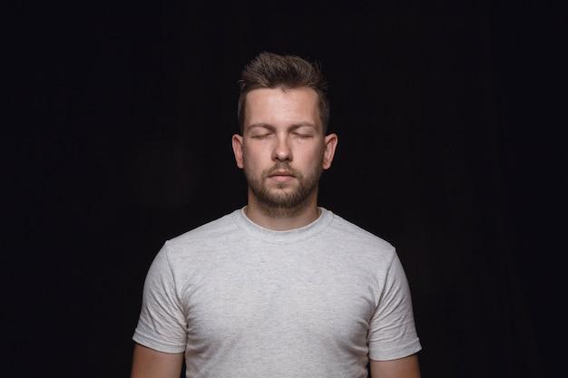 Close-up portret van jonge man geïsoleerd. echte emoties van mannelijk model met gesloten ogen. attent. gelaatsuitdrukking, menselijke aard en emoties concept.