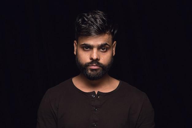 Close-up portret van jonge man geïsoleerd op zwarte muur. echte emoties van mannelijk model. huilend, verdrietig, somber en hopeloos. gelaatsuitdrukking, concept van menselijke emoties.