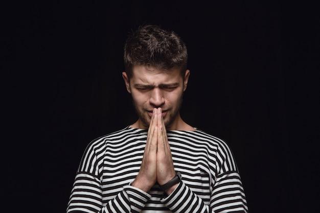Close-up portret van jonge man geïsoleerd op zwarte muur. photoshot van echte emoties van mannelijk model. bidden en huilen, ziet er verdrietig en hoopvol uit. gelaatsuitdrukking, concept van menselijke emoties.