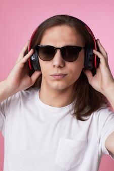 Close-up portret van jonge man in zonnebril luistert naar muziek met koptelefoon en danst op roze achtergrond