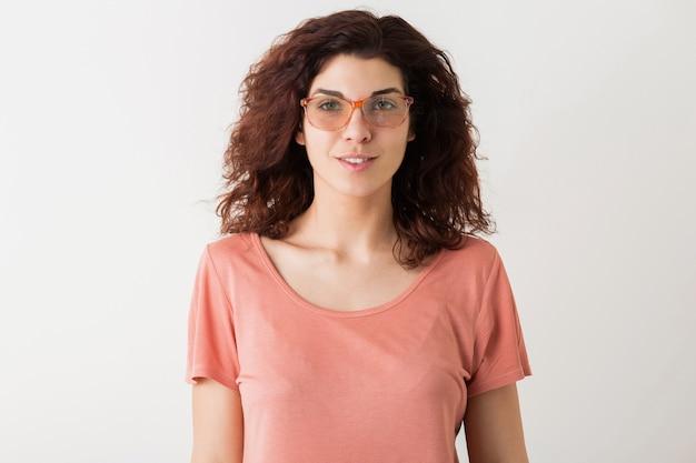 Close-up portret van jonge natuurlijke hipster mooie vrouw met krullend kapsel in roze shirt poseren met bril geïsoleerd op witte studio achtergrond