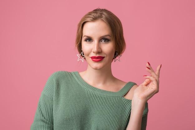 Close-up portret van jonge sexy aantrekkelijke vrouw, stijlvolle make-up, rode lippen, groene trui, model poseren in studio, geïsoleerd, roze achtergrond, oorbellen, in de camera kijken, hand omhoog houden, elegant