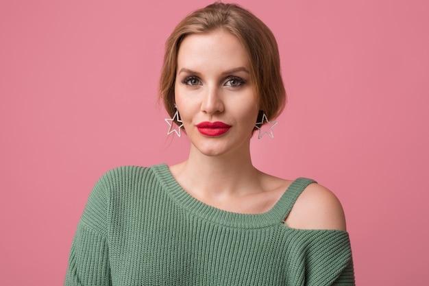 Close-up portret van jonge sexy aantrekkelijke vrouw, stijlvolle make-up, rode lippen, groene trui, model poseren in studio, geïsoleerd, roze achtergrond, oorbellen, in de camera kijken