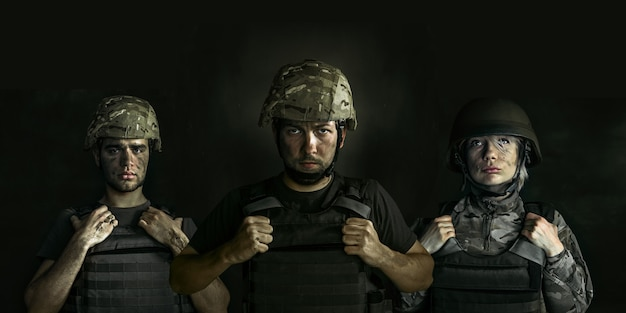 Close-up portret van jonge soldaten. mannen en vrouwen in militair uniform over de oorlog tegen zwarte muur