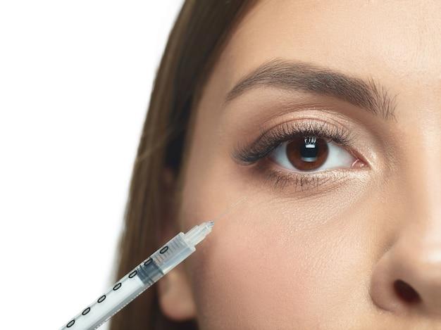 Close-up portret van jonge vrouw geïsoleerd op een witte achtergrond. operatieprocedure vullen.
