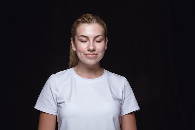 Close-up portret van jonge vrouw geïsoleerd. vrouwelijk model met gesloten ogen. denken en glimlachen. gelaatsuitdrukking, concept van menselijke emoties.