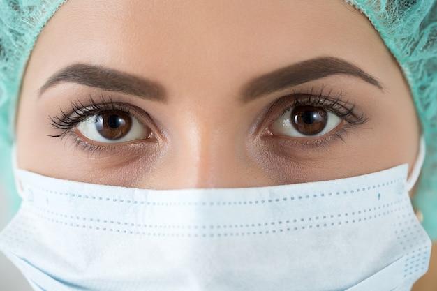 Close-up portret van jonge vrouwelijke chirurg arts of stagiair dragen beschermend masker en hoed. gezondheidszorg, medisch onderwijs, medische noodhulp, chirurgie of veterinair concept