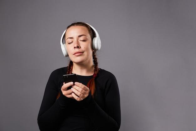 Close-up portret van kaukasische vrouwelijke podcast of muziek luisteren op grijze achtergrond. muziek luisteren via een koptelefoon