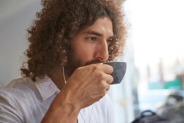 Close-up portret van knappe gekrulde ongeschoren jongeman koffie drinken in café en luisteren naar muziek met koptelefoon, op zoek attent en kalm