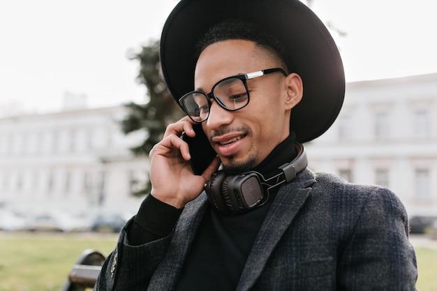Close-up portret van knappe jonge afrikaanse man praten over de telefoon. buiten schot van zwarte man in trendy hoed iemand te bellen.