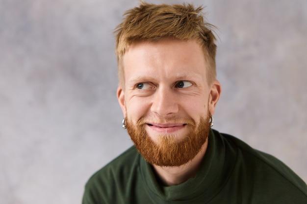 Close-up portret van knappe jonge blanke man met stijlvol kapsel en getrimde baard poseren geïsoleerd wegkijken met mysterieuze glimlach, zeer gevleid voelen. positieve menselijke uitdrukkingen