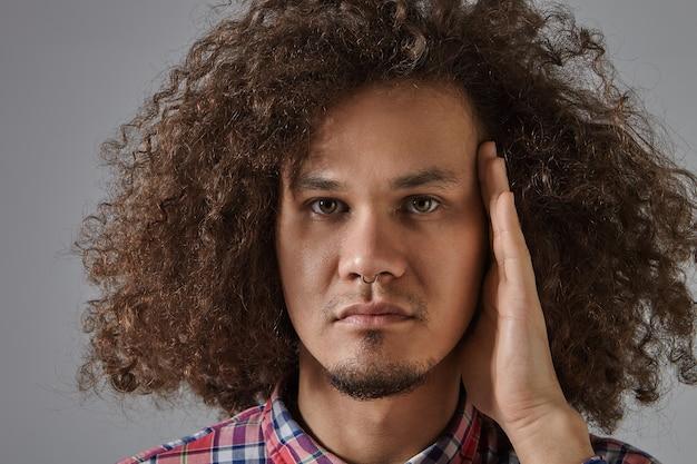 Close-up portret van knappe jonge donkerhuidige man met volumineus haar, bruine ogen, mollige wangen en getrimde baard poseren geïsoleerd met serieuze blik, met de hand op zijn gezicht
