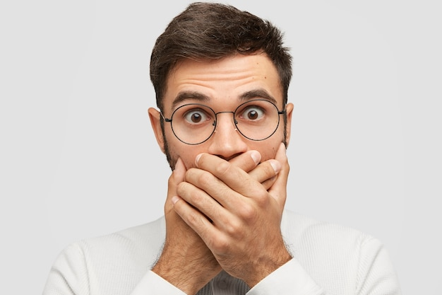 Close-up portret van knappe jongeman bedekt mond met beide handpalmen, probeert te worden gedempt, stopt met schreeuwen