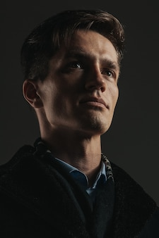 Close-up portret van knappe man op zwart Premium Foto