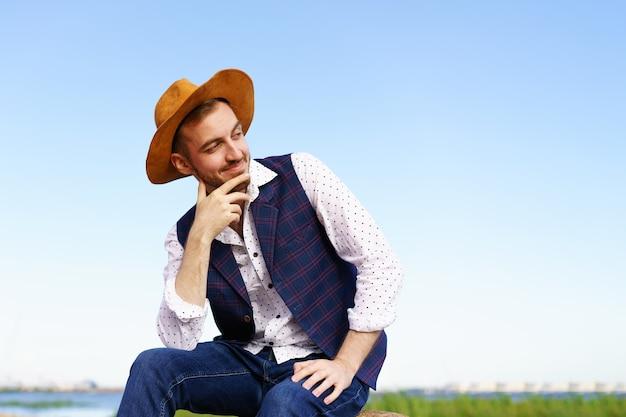 Close-up portret van knappe stijlvolle casual man reiziger in hoed zittend aan de kust van de zee en geniet...