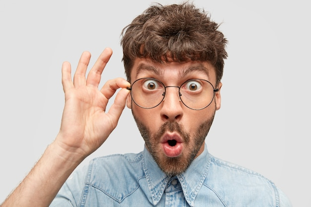 Close-up portret van knappe verbaasde man met dikke stoppels, verbijsterd door bril staart