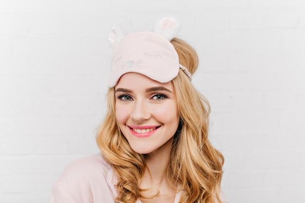 Close-up portret van lachen prachtige vrouw in schattig eyemask. tevreden europees vrouwelijk model in pyjama die van goedemorgen op witte muur geniet.