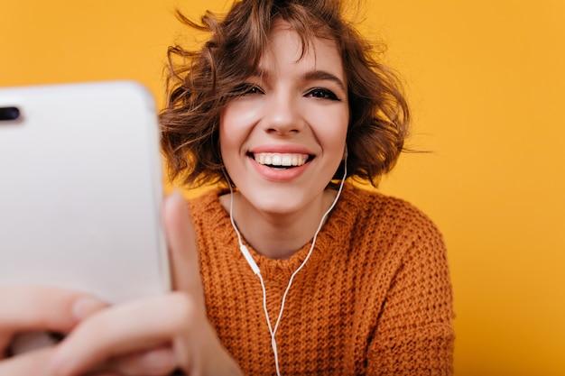 Close-up portret van lachen wit meisje met telefoon voor selfie