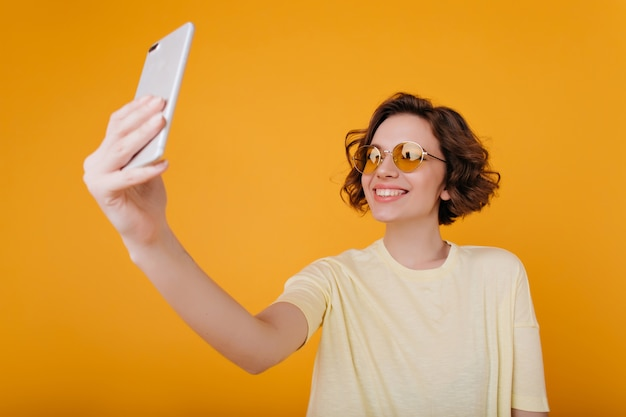 Close-up portret van lachende brunette meisje met golvend kapsel selfie maken