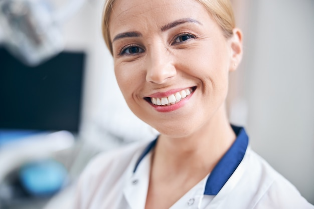 Close-up portret van lachende jonge vrouw in medische mantel die op kantoor staat en geniet van haar baan